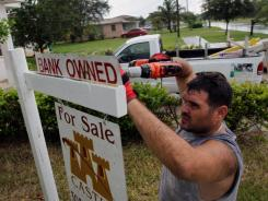 Renzo Salazar places a bank owned sign on top of a for sale sign by a foreclosed home in Miami on Oct. 13.