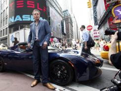 Elon Musk, CEO of Tesla Motors, poses with a Tesla car in front of Nasdaq following the electric automaker's IPO in June 2010.