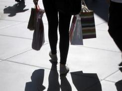 A shopper carrying bags is silhouetted at a mall in Los Angeles.