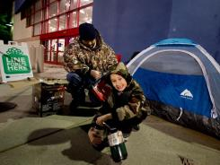 Brent Hart fires up a propane heater with son Aidan as he camps out Wednesday in advance of Black Friday outside a Best Buy in Fairfax, Virginia.