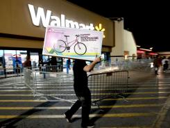 A shopper walks to his car after purchasing a bike at Walmart on Thursday in Gainesville, Fla.