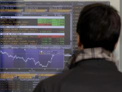 A man looks at oil, bond and stock prices on a screen of a bank in Milan, Italy, on Monday, Nov. 28, 2011.
