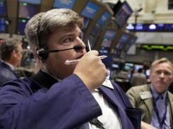 Trader Stephen Perciballi, left, works on the floor of the New York Stock Exchange, Nov. 28, 2011.