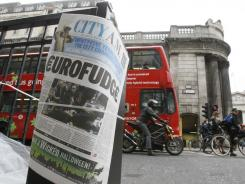 A financial newspaper is fixed to a pillar in London across from The Bank of England.