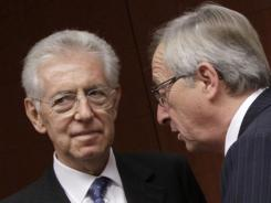 Luxembourg's Prime Minister Jean-Claude Juncker, right, speaks with Italian Prime Minister Mario Monti at a eurogroup meeting at the EU Council building in Brussels on Nov. 29, 2011.
