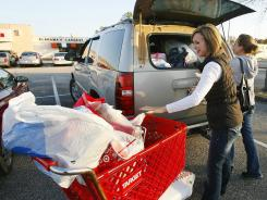 In this Nov. 25, 2011 photo, Rhonda Cochran, left, and Tiffany Strickland load bags of Black Friday deals into a car at Bel Air Mall in Mobile, Ala.