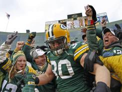 Green Bay Packers fullback John Kuhn celebrates a touchdown with a Lambeau Leap into the hometown stands Nov. 20, 2011.