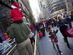 Shoppers and window display watchers fill the sidewalks Nov. 26 in front of Saks Fifth Avenue in New York City.
