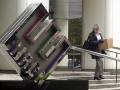 A woman carries a box from Enron's Houston headquarters on Nov. 28, 2001, as speculation of the company's bankruptcy grew.