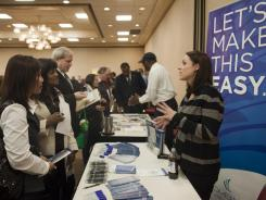 Elizabeth Walton introduces her insurance company to potential new employees at a job fair Friday in Portland, Ore.