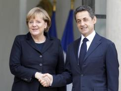 French President Nicolas Sarkozy, right, shakes hands with German Chancellor Angela Merkel at the Elysee Palace in Paris on Dec. 5, 2011.