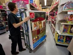 A stock clerk working on Black Friday moves merchandise into position at the  Fair Lakes Shopping Center on Nov. 24, 2011, in Fairfax, Va.