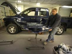Tom O?Mara of O'Mara Auto Body works on a door repair at his shop in Martensdale, Iowa.