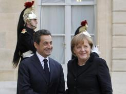 French President Nicolas Sarkozy, left, welcomes German Chancellor Angela Merkel, Dec. 5, 2011, for a key EU summit Friday, at the Elysee Palace, Paris,