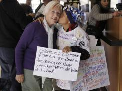 A homeowner facing foreclosure gets a kiss from a protester in Redwood City, Calif., on Dec. 6, 2011.