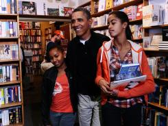 President Obama and daughters Malia, right, and Sasha on Nov. 26 at Kramerbooks and Afterwords, a local bookstore in Washington.