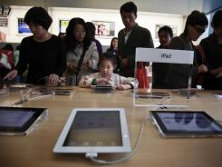 A girl tries out an iPad at an Apple store in Beijing on Oct. 6, 2011.
