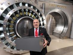 The Coca-Cola Co. CEO Muhtar Kent holds the safe-deposit box containing the 125-year-old secret formula for Coca-Cola in front of the entrance to a new permanent exhibit at the World of Coca-Cola in Atlanta.