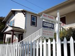"""A """"sale pending"""" sign is posted in front of a home for sale on Nov. 30 in San Rafael, Calif."""