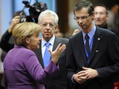German Chancellor Angela Merkel, Italian Prime Minister Mario Monti, center, and a delegation member Friday at the EU summit in Brussels.