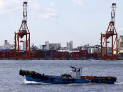 A boat passes before a container terminal at the port of Tokyo.