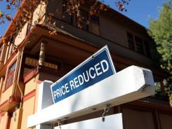 "A ""price reduced"" sign is posted in front of a home for sale on Nov. 30, 2011, in San Rafael, Calif.."