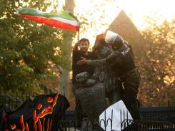 A policeman speaks with a protester waving the Iranian national flag Nov. 29 from a gate at the British embassy in Tehran.