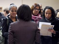 Jobseekers talk with a recruiter at a job fair in New York City on Dec. 12, 2011.