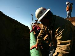 A crew from Alpha Oil & Gas Services constructs a 10-inch gas pipeline outside  Watford City, N.D,