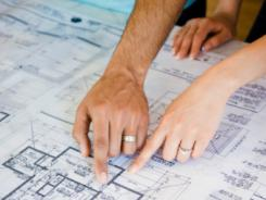 Couple pointing to blueprints.