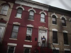 Residents in front of foreclosed rowhouses in Brooklyn, N.Y., on Dec. 6, 2011.