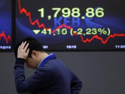 A currency trader watches markets in front of a screen showing Korea's  Composite Stock Price Index in Seoul on Monday.