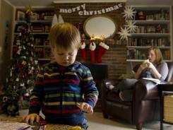 Griffin Holland, with mom Sarah Stewart Holland, plays in his family's Paducah, Ky., home on Dec. 14. The family has scaled back on Christmas spending, and Griffin will get gifts stashed after his birthday celebration.