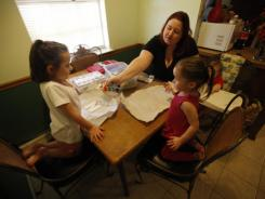 Chasity Robinson paints Christmas ornaments with her children Nevaeh, 5, Emma, 3, and J.J., 1.