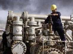 Iraqis work at an oil refinery near Baghdad. The country's oil industry has attracted widespread interest from foreign companies.