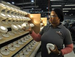 An inspector looks over LED bulbs made at Lighting Sciences Group in Satellite Beach, Fla.
