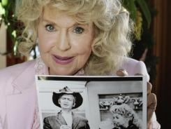 "Donna Douglas, who starred as Elly Mae Clampett in the TV series ""The Beverly Hillbillies"" poses with a photo from the show in Baton Rouge, La., in January 2009."
