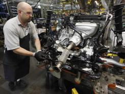 A line worker moves an engine on the assembly line for a Ford Focus at the Ford assembly plant in Wayne, Mich., on Dec. 14, 2011.
