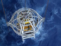 An underwater robot is lowered into the water 8,000 feet to work on equipment on the sea floor, 200 miles off the coast of Texas, in October 2011.