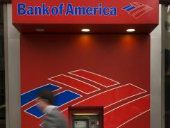 A pedestrian walks past an ATM near the Bank of America headquarters in Charlotte, N.C., in February 2010.