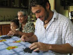 Peace Corps volunteer Mick Wigal of Youngstown, Ohio, sorts beans with his host family in Costa Rica. Nick Paddock, another Peace Corps volunteer, will spend 27 months in Thailand.