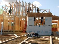 Construction workers put together an apartment building in Williston, N.D.