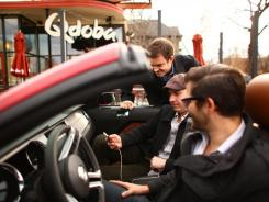 Front to back, Roximity's Danny Newman, Austin Gayer and Joe Mease test a company app in a Ford Mustang GT outside a Denver restaurant.