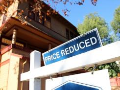 "Home prices remain relatively weak as a ""price reduced"" sign is posted in front of a home for sale in November 2011, in San Rafael, Calif."