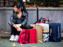 A consumer rests in Herald Square during the busiest shopping day of the year, Nov. 25, in New York.