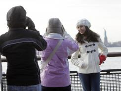 Brazilian tourists take pictures in front of the Statue of Liberty in New York harbor Jan. 4, 2012.
