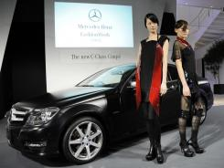 Models wear outfits designed by Kentaro Fujiki inspired by Mercedes-Benz's C-class Coupe during the vehicle's Japan premiere.