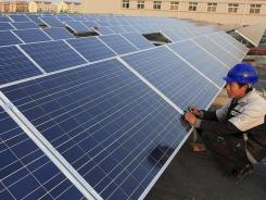A worker fixes a solar panel at a factory in Qingdao, in east China's Shandong Province.