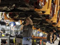 A line worker assembles a Ford Focus at the Ford Michigan Assembly plant in Wayne, Mich, on Dec. 14, 2011.