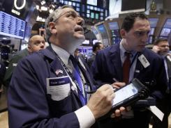 Warren Meyers, left, works with fellow traders on the floor of the New York Stock Exchange on Jan. 10, 2012.